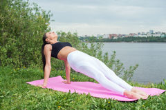 Woman doing Hatha yoga asana Purvottanasana plank pose outdoors. Royalty Free Stock Photography