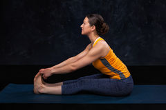 Woman doing Hatha yoga Ashtanga Vinyasa yoga asana Paschimottana. Sana - seated forward bend beginner variation on dark grunge background royalty free stock image
