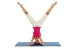 Woman Doing A Headstand. On A Yoga Mat Royalty Free Stock Images