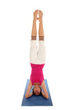Woman Doing A Headstand. On A Yoga Mat Royalty Free Stock Photography