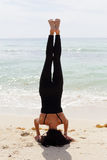 Woman doing a headstand on the beach Royalty Free Stock Images