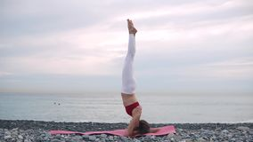 Woman doing headstand on beach on yoga mat. stock video footage