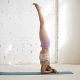 Woman doing headstand in sunny room Stock Photo
