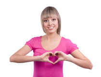 Woman doing a heart symbol with her hand. Beautiful young woman in pink dress making a hand frame with heart shape. Girl doing a heart symbol with her hand Stock Photo