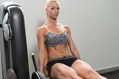Woman Doing Heavy Weight Exercise For Quadriceps. Leg Exercises - Young Woman Doing Leg With Machine In Gym Stock Photo
