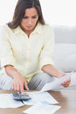 Woman doing her accounts. Sat on a couch stock photography