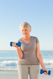 Woman doing her exercises at the beach Stock Photo