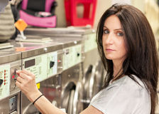 Woman doing her laundry in a laundromat Royalty Free Stock Photo