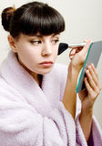 Woman is doing her make up. Young beautiful woman is doing her make up Stock Photography