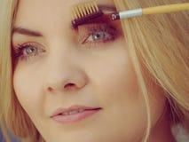 Woman brushing her eyebrows royalty free stock photos