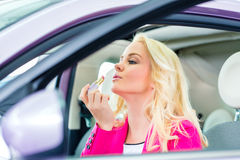 Woman doing her makeup in car Royalty Free Stock Photo