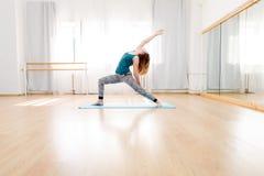 Woman doing high lunge yoga asana in light spacious studio. Young woman doing high lunge yoga asana in light spacious studio, virabhadrasana royalty free stock image