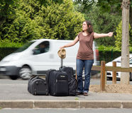 Woman doing the hitchhiking. A young woman doing the hitchhiking, hope to go on vacation Royalty Free Stock Photos