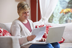 Woman doing home banking. Woman looking happy while sitting at home doing home banking with laptop stock photo