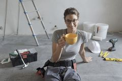 Woman doing a home renovation and having a coffee break royalty free stock photos