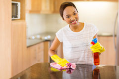 Woman doing house chores. Beautiful young african woman doing house chores royalty free stock photo