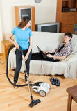 Woman doing house cleaning during man resting Stock Photo