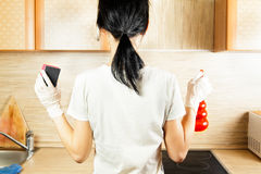 Woman doing housekeeping. Rear view of woman with gloves in kitchen doing housework Royalty Free Stock Image