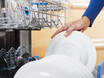 Woman doing housework. Close up of woman in kitchen using dishwasher stock photo