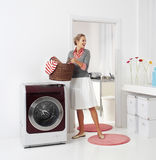 Woman doing a housework. Holding basket of laundry royalty free stock photo