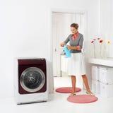 Woman doing housework holding presoak. Woman doing a housework holding presoak Stock Photos