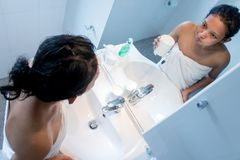 Woman doing hygiene before a mirror. Girl gargle and looking on reflection in the mirror in bathroom. Woman doing hygiene before a mirror wrapped in a towel royalty free stock image