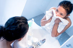 Woman doing hygiene before a mirror. Girl looking on reflection in the mirror in bathroom. Woman doing hygiene before a mirror wrapped in a towel stock images