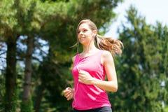 Woman doing jogging outdoors Stock Photos