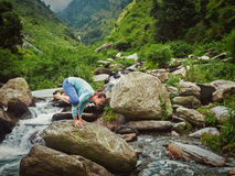 Woman doing Kakasana asana arm balance at waterfall Stock Photography