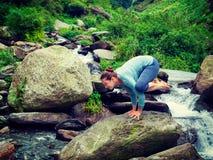 Woman doing Kakasana asana arm balance at waterfall Royalty Free Stock Image
