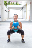 Woman doing the kettlebell squat for muscle strengthening exercise Stock Image