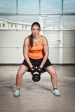 Woman doing kettlebells pull up. In a gym stock images