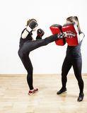 Woman doing kick boxing. Young women learning kick boxing, self defense martial arts Stock Photos