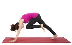 Woman doing knee to head pose in downward facing dog pose Royalty Free Stock Photos
