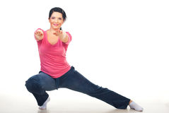 Woman doing lateral lunge. And standing with hands outstretched on floor over white background royalty free stock images