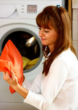 Woman doing laundry. A beautiful woman doing laundry in her home (house) holding orange clothes, closeup shot Stock Image