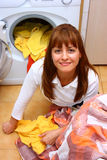 Woman doing laundry. A smiling woman doing laundry in her home (house) sitting on the floor stock images