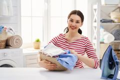 Woman is doing laundry. Beautiful young woman is smiling while doing laundry at home stock images
