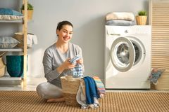 Woman is doing laundry. Beautiful young woman is smiling while doing laundry at home stock photos