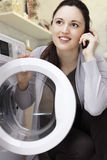 Woman doing laundry. Caucasian woman in her 30's talking on the cell phone while doing laundry stock images