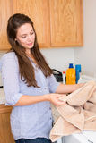 Woman doing laundry. Happy woman doing laundry in her home Royalty Free Stock Photos
