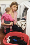 Woman Doing Laundry And Holding Daughter. Woman Doing Laundry And Holding Baby Daughter Royalty Free Stock Photo
