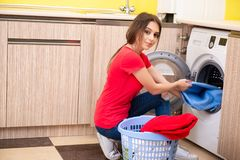 The woman doing laundry at home. Woman doing laundry at home stock photo