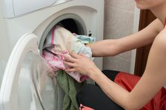 Woman doing laundry at home loading clothes to the washing machine Royalty Free Stock Photos