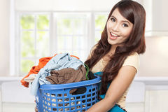 Woman doing laundry. Woman doing a housework holding laundry Royalty Free Stock Image