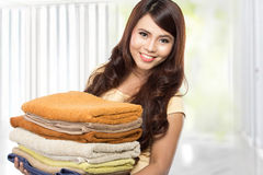 Woman doing laundry. Woman doing a housework holding laundry and smiling Stock Photo