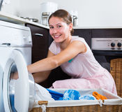 Woman doing laundry. Positive young woman doing laundry and smiling royalty free stock image