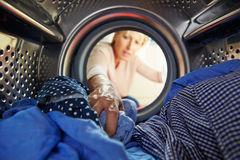 Woman Doing Laundry Reaching Inside Washing Machine Stock Photo