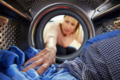 Woman Doing Laundry Reaching Inside Washing Machine Royalty Free Stock Images