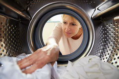 Woman Doing Laundry Reaching Inside Washing Machine Royalty Free Stock Photography